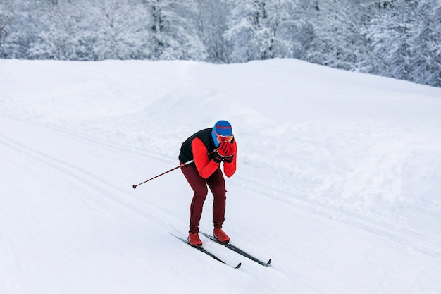 Uno sciatore in tuta rossa, passamontagna blu e occhiali di sicurezza che cavalca velocemente in discesa