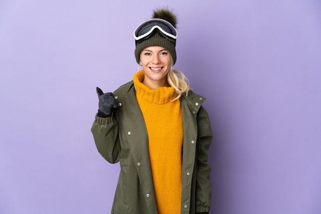 Sciatore ragazza russa con occhiali da snowboard isolati su sfondo viola che punta di lato per presentare un prodotto
