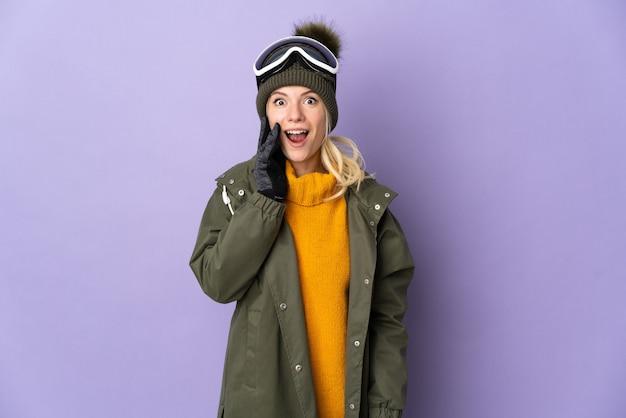 Sciatore ragazza russa con occhiali da snowboard isolati su sfondo viola con espressione facciale sorpresa e scioccata