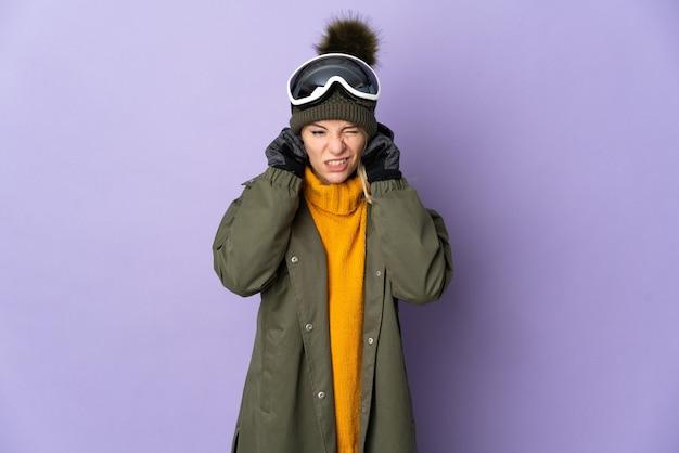 Sciatore ragazza russa con occhiali da snowboard isolati su viola frustrato e che copre le orecchie