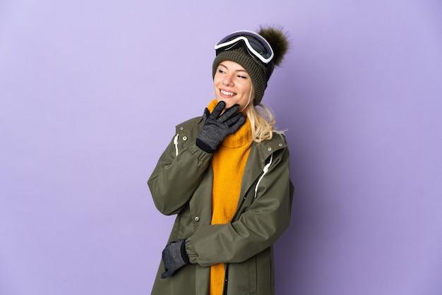 Sciatore ragazza russa con occhiali da snowboard isolati su viola alzando lo sguardo mentre sorridendo