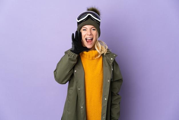 Sciatore ragazza russa con occhiali da snowboard isolati su viola che grida con la bocca spalancata