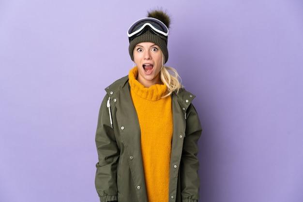 Sciatore ragazza russa con occhiali da snowboard isolato sulla parete viola con espressione facciale a sorpresa