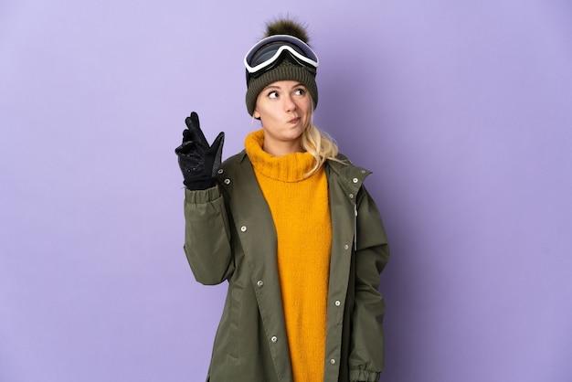 Sciatore ragazza russa con occhiali da snowboard isolati su viola con le dita che si incrociano e che desiderano il meglio