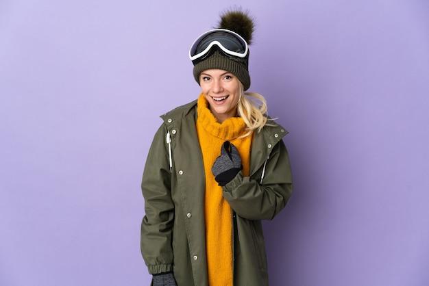 Sciatore ragazza russa con occhiali da snowboard isolati su viola con espressione facciale a sorpresa