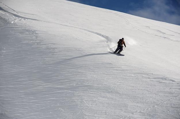Lo sciatore in abbigliamento sportivo speciale scivola rapidamente giù per le montagne con tempo sereno