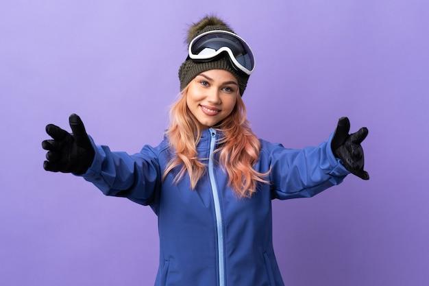 Ragazza dell'adolescente dello sciatore con gli occhiali dello snowboard sopra fondo viola isolato che presenta e che invita a venire con la mano