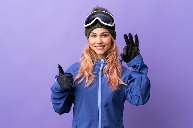 Ragazza dell'adolescente dello sciatore con gli occhiali dello snowboard sopra fondo viola isolato che mostra segno giusto e pollice sul gesto