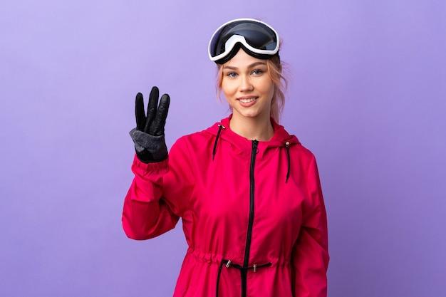 Ragazza dell'adolescente dello sciatore con gli occhiali dello snowboard sopra la parete viola isolata felice e contando tre con le dita