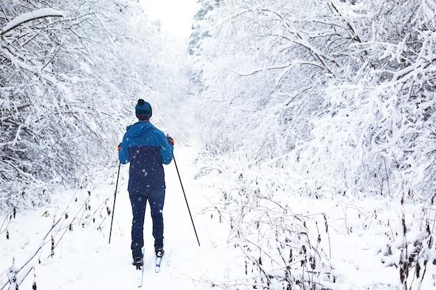 Sciatore in giacca a vento e cappello con pompon con bastoncini da sci in mano