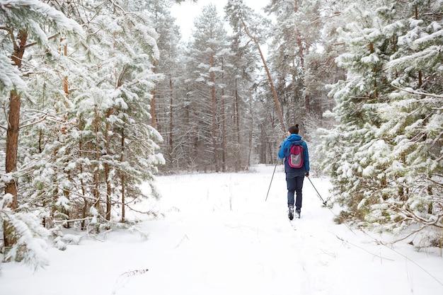 Sciatore con zaino e cappello con pompon con bastoncini da sci in mano
