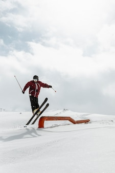 Sciatore con attrezzatura che salta pieno colpo