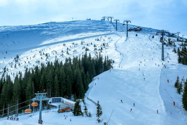 Sciatori sulle piste da sci. due linee di uno skilift. il sole irrompe a malapena tra le nuvole