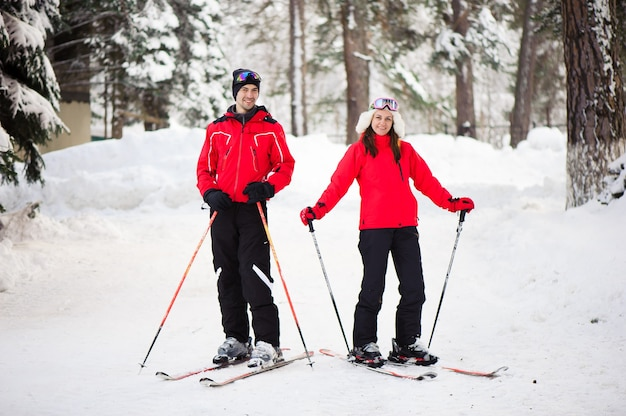 Sci, neve, divertimento invernale, famiglia felice è sciare nella foresta.