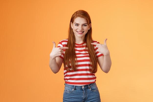 Abile bella ragazza rossa motivata che si indica indica le dita petto che si vanta gioiosamente...