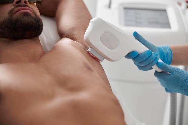 Abile cosmetologo utilizza attrezzature moderne per rimuovere i peli dall'ascella del cliente sportivo