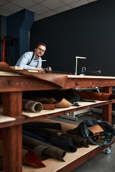 Lavoratore esperto di fabbricazione di cuoio che taglia alcuni campioni nello studio dell'officina.
