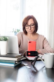 Abile donna di mezza età che comunica online o studia a distanza per telefono sul treppiede,