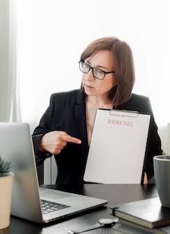 Abile donna di mezza età che comunica online, studia a distanza o lavora nell'ufficio di reclutamento.