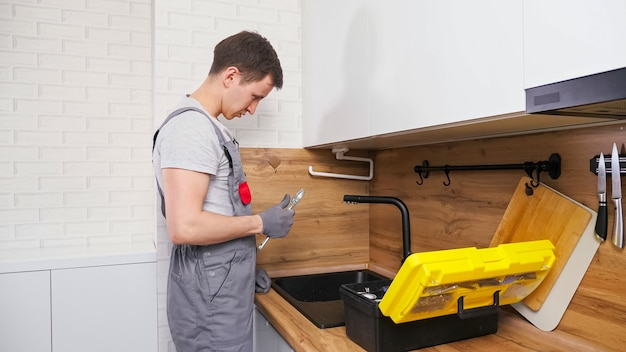 Un idraulico esperto in uniforme grigia con una grande cassetta degli attrezzi viene a controllare e riparare il rubinetto rotto sopra il lavandino nero in una cucina leggera contemporanea