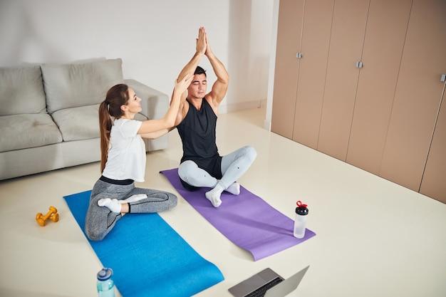 Giovane donna esperta che aiuta il suo ragazzo con la posizione yoga