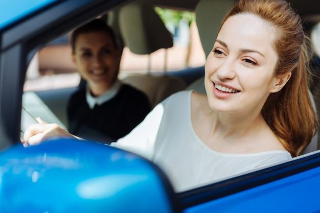 Abile autista. felice bella donna felice sporgendosi dalla finestra e sorridendo mentre si gode il suo giro in macchina