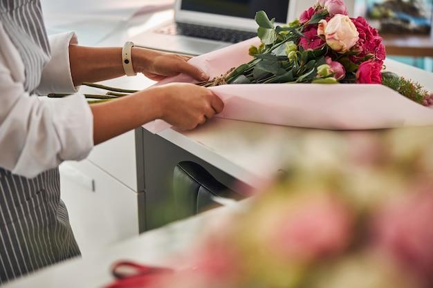 Abile fiorista che copre una composizione di fiori in un involucro di carta rosa