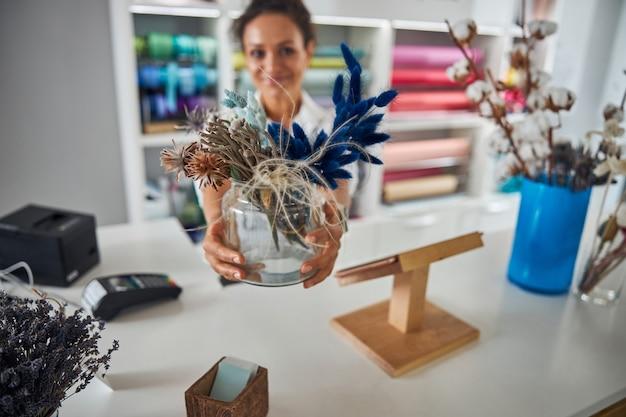 Abile lavoratore del negozio di fiori che tiene un vaso di vetro con fiori