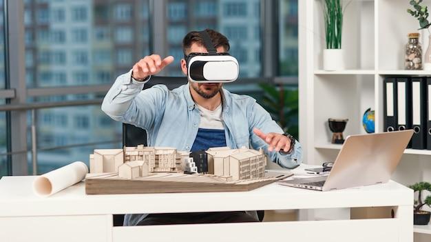 Abile architetto maschio che rivede il progetto architettonico con occhiali vr presso un ufficio moderno.