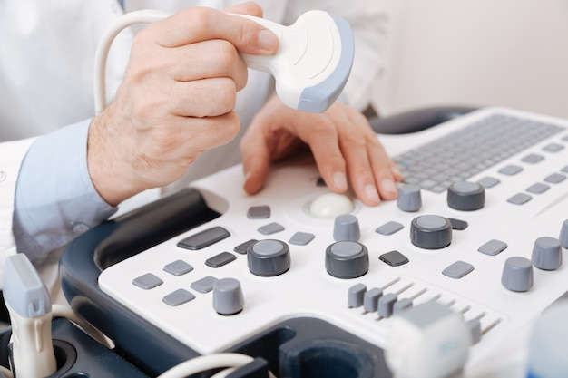 Abile professionista qualificato che lavora nella clinica e utilizza il trasduttore lineare a ultrasuoni durante il controllo delle apparecchiature ecografiche