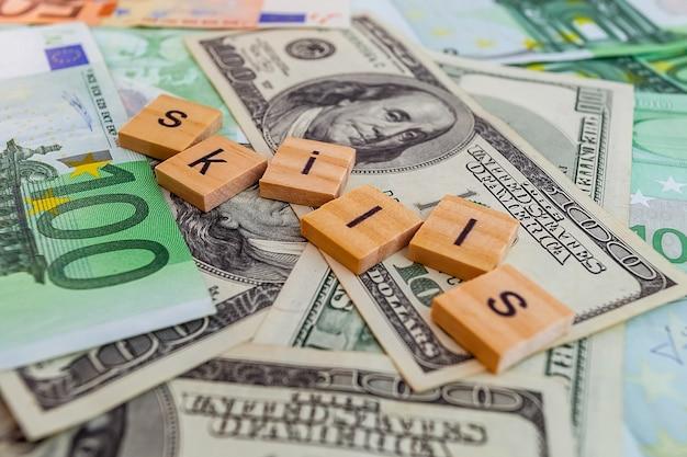 Iscrizione di abilità su cubi di legno sulla trama di dollari americani e banconote in euro