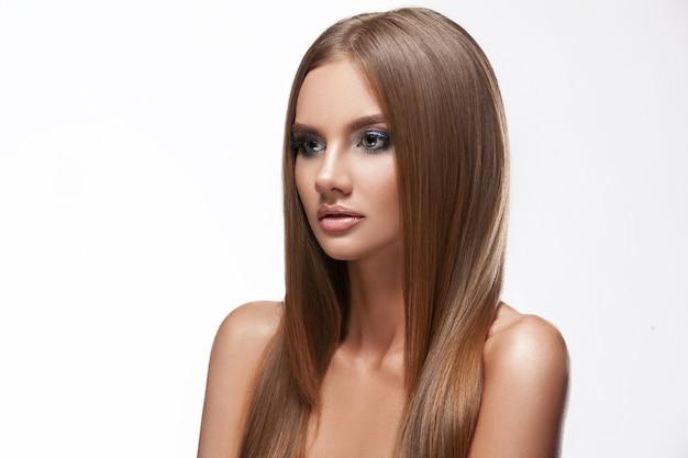 Volto femminile di bellezza della pelle, capelli lisci. ritratto del primo piano di un modello di giovane ragazza. bellissimo trucco, girato su sfondo bianco isolato.