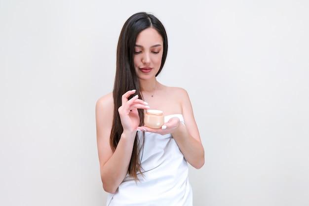 Cura della pelle e del corpo. la bella giovane donna in un asciugamano usa la crema in un barattolo