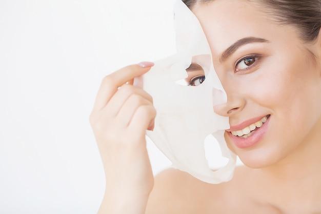 Cura della pelle. bella ragazza con foglio maschera sul viso
