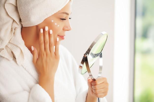 Cura della pelle, bellissima modella che applica un trattamento di crema cosmetica sul viso.