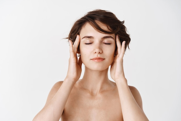 Cura della pelle. bella donna che tocca delicatamente le tempie della testa e chiude gli occhi, gode di una sensazione di viso pulito e idratato dopo i cosmetici per il trattamento del viso, muro bianco