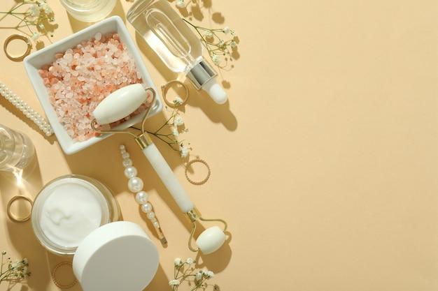 Concetto di bellezza per la cura della pelle con rullo facciale su sfondo beige