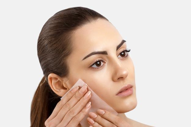 Cura della pelle bellezza viso donna che rimuove l'olio dal viso utilizzando carte assorbenti