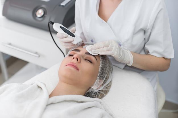 Cura della pelle. primo piano di bella donna che riceve il peeling facciale di cavitazione ad ultrasuoni. procedura di pulizia della pelle ad ultrasuoni. trattamento di bellezza. cosmetologia. salone della stazione termale di bellezza.