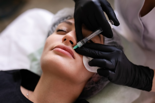 Concetto di cura della pelle. una donna in un salone di bellezza durante un trattamento di cura della pelle del viso.