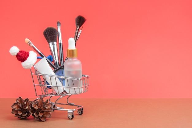 Cosmetici per la cura della pelle e pennelli per il trucco in un carrello della spesa a natale