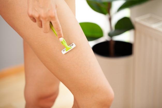Cura della pelle e salute, donna in forma che rade le gambe con il rasoio.