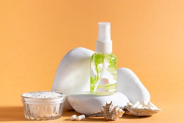 Lozione o siero per la cura della pelle con estratto di piante marine e collagene su podio di pietra