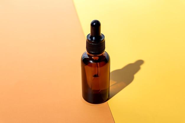 Siero per la cura della pelle in flacone contagocce in vetro ambrato su sfondo beige e giallo. design del packaging del prodotto di bellezza naturale biologico spa.