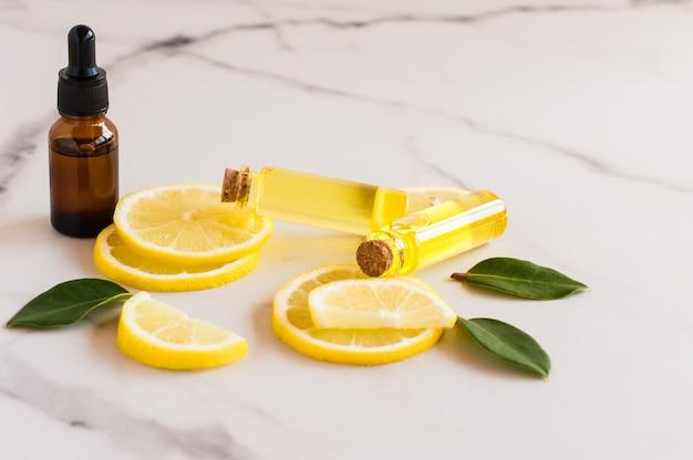 Siero per la cura della pelle e oli essenziali di limone su un tavolo di marmo. idratante, aromaterapico, effetto antistress.