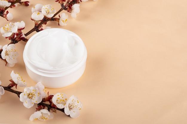 Crema mani bianca per la cura della pelle e ramo primaverile