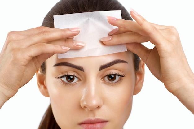 Cura della pelle donna che rimuove l'olio dal viso utilizzando carta assorbente
