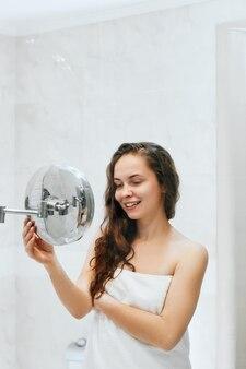 Cura della pelle. donna che tocca i capelli e sorridente mentre guardandosi allo specchio.ritratto di ragazza felice con i capelli bagnati in bagno