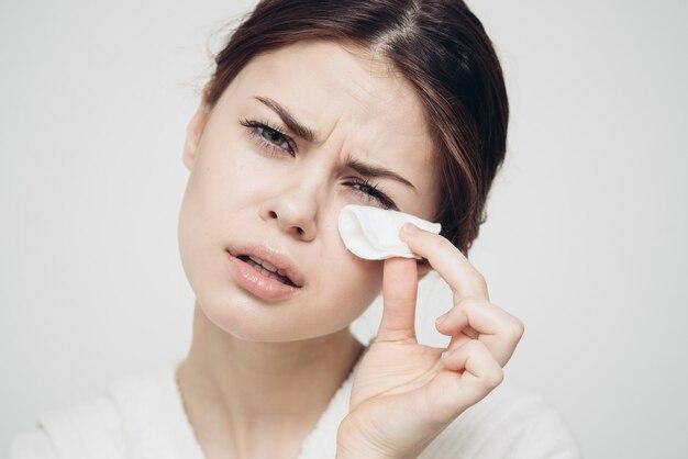 La donna di cura della pelle si pulisce il viso con una spugna bianca