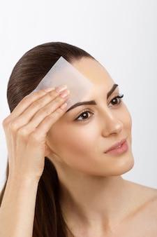 Cura della pelle giovane donna che rimuove l'olio dal viso utilizzando carta assorbente